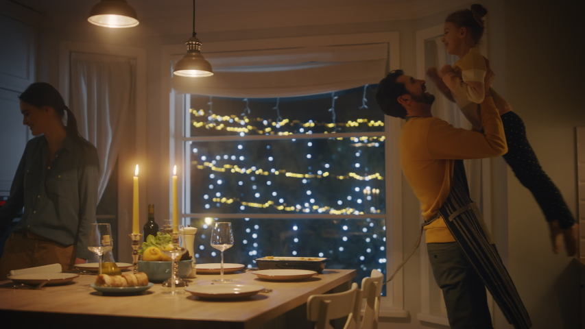Happy Family of Three Cooking and Having Dinner Together. Mother Prepares Food, Cute Little Girl Runs to Father, Hugs Him and They Dance. Festive Table in Cozy Kitchen Interior. Slow motion