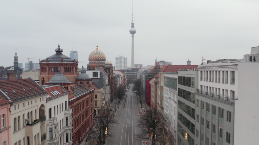 AERIAL: Slow flight trough Empty Central Berlin Neighbourhood Street with Cathedrals and view on Alexanderplatz TV Tower during Corona Virus COVID19 on Overcast Cloudy Day