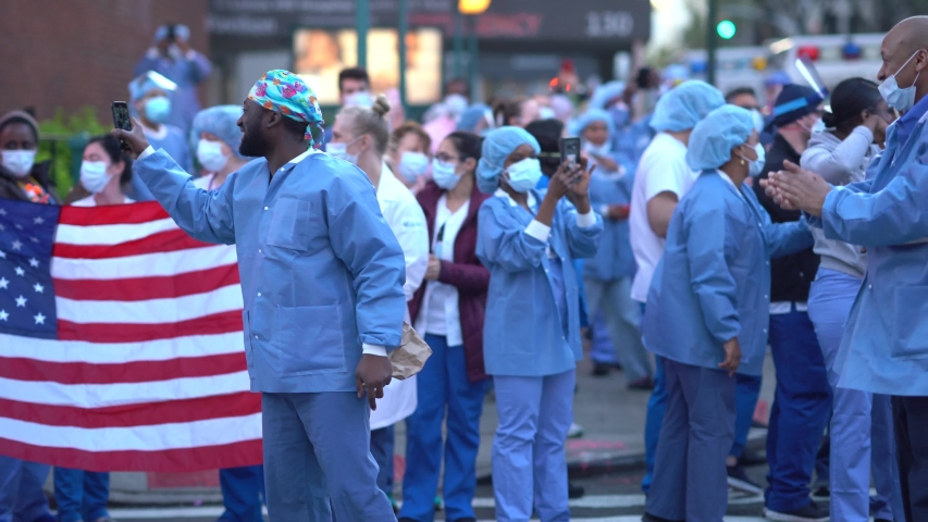 New York City, New York / USA - April 17 2020: New York hospital healthcare workers and nurses clapping expressing gratitude for saving lives during pandemic coronavirus outbreak in New York City.
