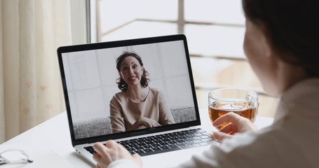 Happy older middle aged parent mother talking with young adult woman daughter by web camera video call, family remote online chat on laptop computer screen. Videocall concept. Over shoulder closeup