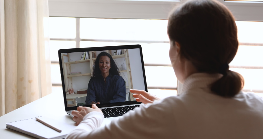 Diverse business women video calling working from home office. Over shoulder laptop screen view of female recruiter, hr manager interviewing african candidate, consulting client in webcam virtual chat Royalty-Free Stock Footage #1050675430