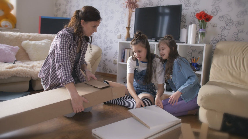 Happy family unpacking box together with new furniture. | Shutterstock HD Video #1050676924