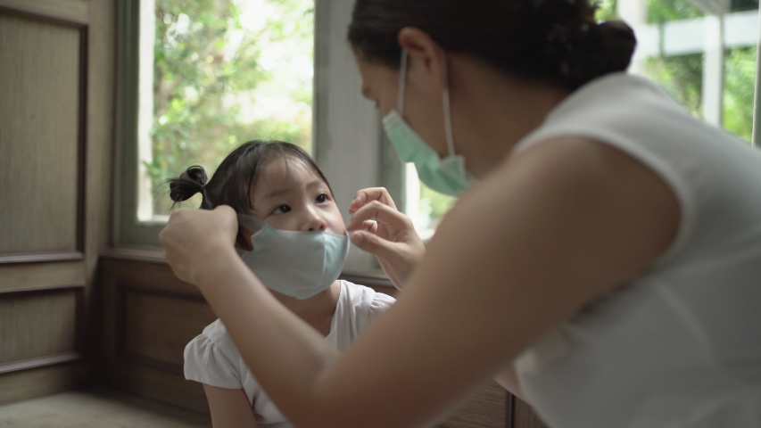 Asian mother wearing medical face mask for daughter. COVID-19, Handheld shot | Shutterstock HD Video #1050692755