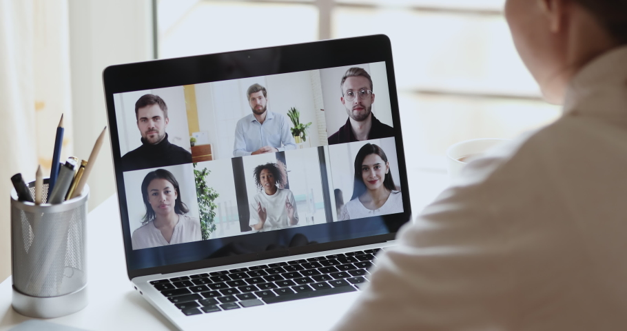 Diverse business people group conferencing in online chat on laptop screen. Over shoulder view of female remote worker video calling working from home office. Team virtual meeting by web cam concept Royalty-Free Stock Footage #1050707059