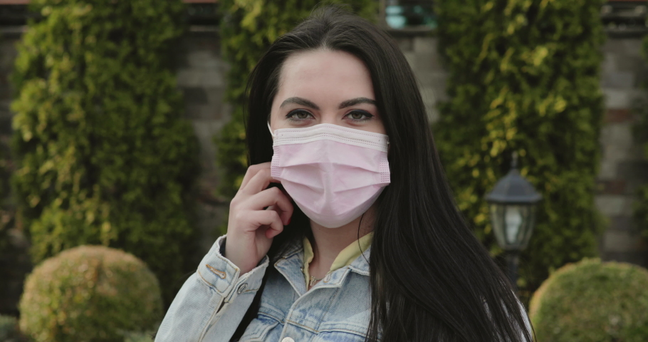 Portrait of cured, girl in windy garden undresses medical mask, corrects hair and smiles at camera. 4K | Shutterstock HD Video #1050707827