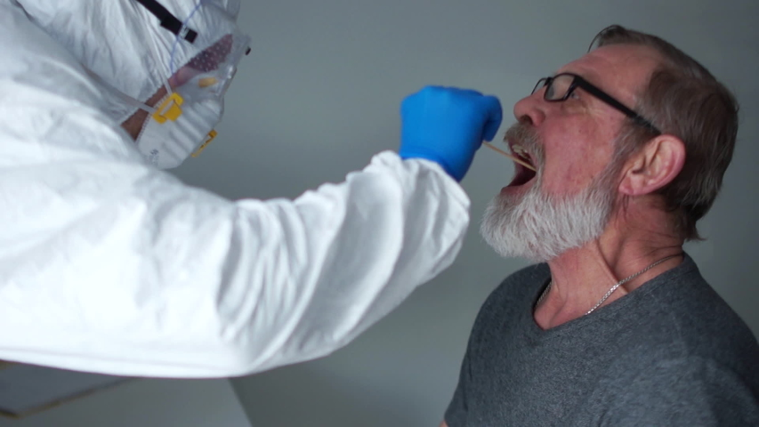 Coronovirus test family risk group. Doctor in a protective suit takes a swab from the throat from an elderly woman pensioner then from her husband. Non-invasive diagnostic method by PCR reaction Royalty-Free Stock Footage #1050710329