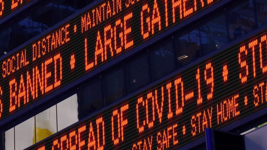 Closeup view of a Times Square ticker says stay safe and say home and large gatherings are banned. Physical distancing was a common practice to slow the spread of COVID-19 during the pandemic of 2020. Royalty-Free Stock Footage #1050713545