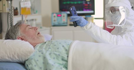 A nurse or doctor in full PPE helps a hospitalized patient with COVID19 keep in touch with his family via a video conference on a cell phone.