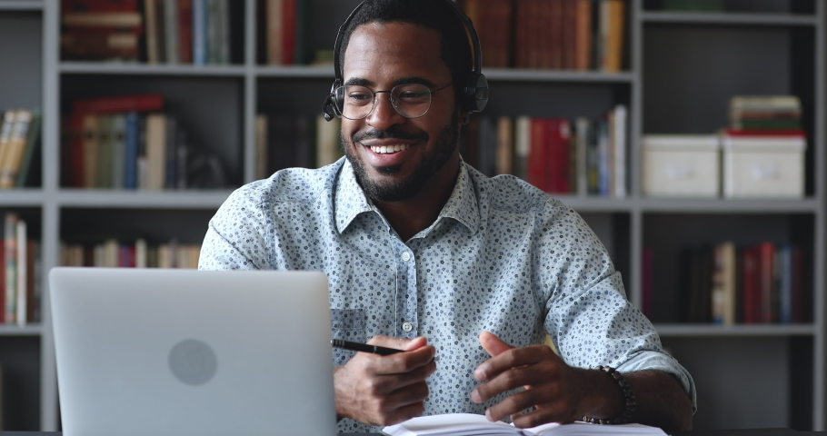 Happy young african american guy in glasses wearing wireless headphones with microphone, looking at laptop, holding video call talking speaking with consultant teacher mentor coach, writing notes. Royalty-Free Stock Footage #1050724894