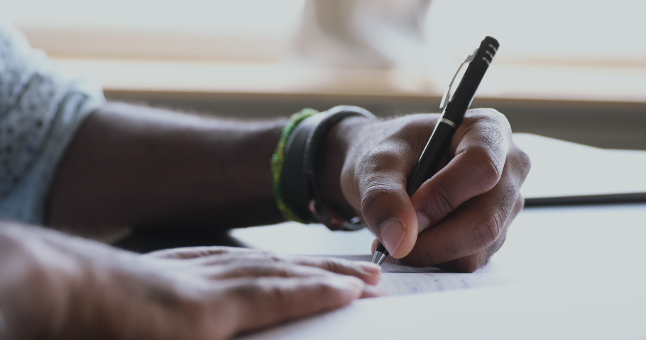 Close up side view millennial biracial man writing down notes in paper notepad, sitting at table. Young left handed entrepreneur businessman making appointments daily tasks in personal organizer. | Shutterstock HD Video #1050726373