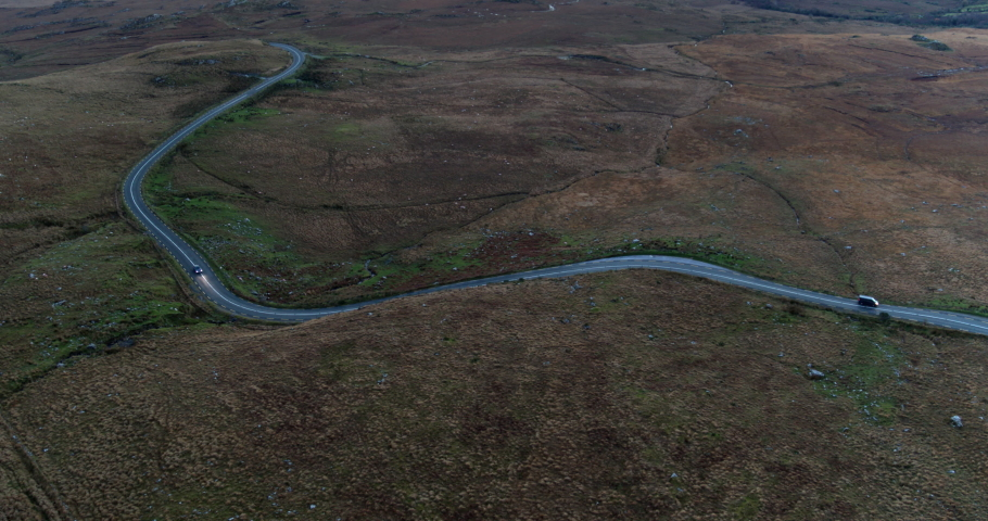 Aerial view of Kerry Road in Ireland. Vast, dry landscape. Cars driving on road.   Shutterstock HD Video #1050727846