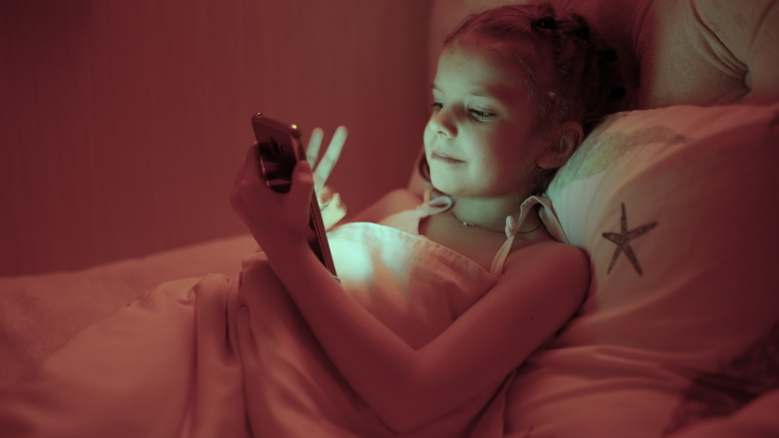Cute Little Girl in Her Room at Night, Lies on a Bed Uses Smartphone. | Shutterstock HD Video #1050732079