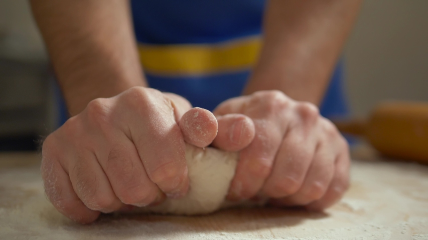 SHALLOW DEPH: Male hands kneading dough in flour on the table. Close up view of baker hands kneading the dough on the table. Manufacturing process, working hard. Making bread, bread production. Royalty-Free Stock Footage #1050734914