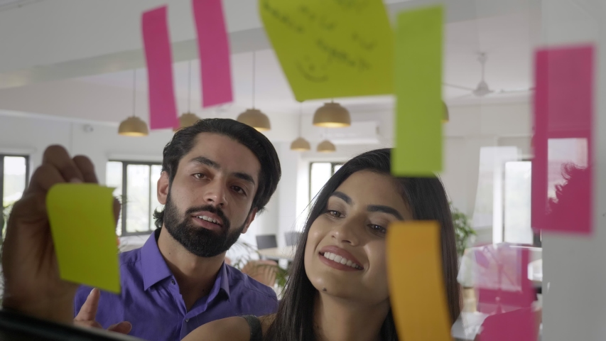 A smiling happy office corporate woman female girl using sticky notes for brainstorming session with male man colleague employee worker. A businesswoman leader planning with business partner.