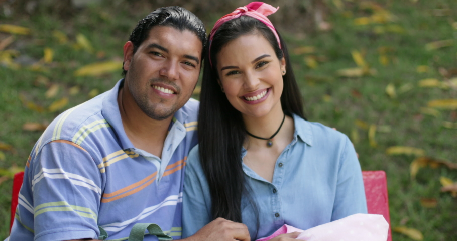 Slow Motion Portrait of Young Hispanic Smiling Couple With Their Newborn Baby Infant Sitting Outdoors On a Bench of a Public Park During a Sunny Day Looking at Camera 4k