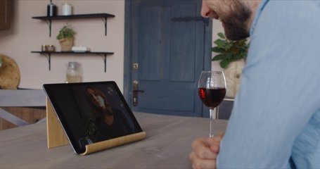 Handsome Caucasian man having a glass of wine during video call with girlfriend. Stay home, quarantine life