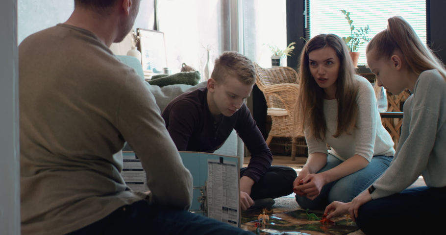 Family - father, mother and two kids playing a board game together. Stay home, quarantine. Board game is custom made for the shot. RED Dragon Royalty-Free Stock Footage #1050747817