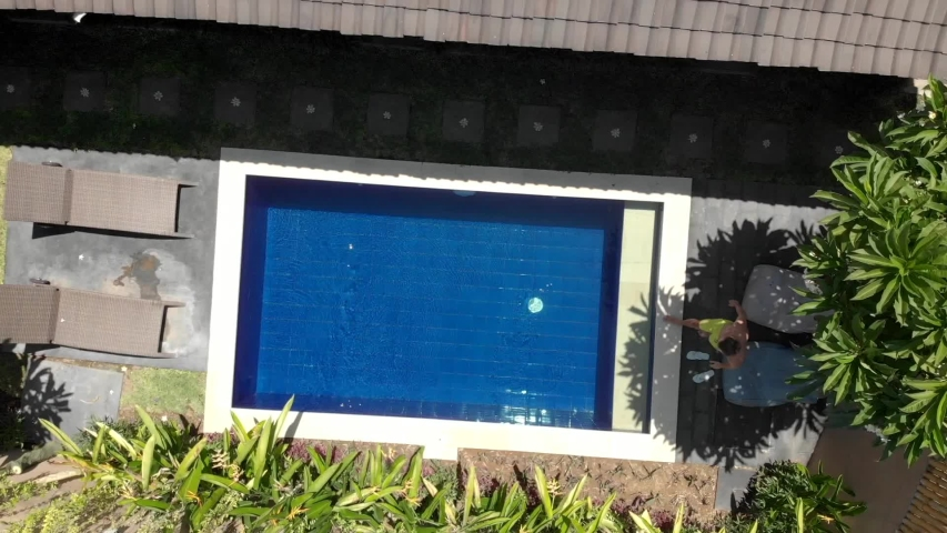 Drone zoom out young man jumping to the small blue swimming pool and roll over on his back. Top view of swimming pool in guesthouse in Bali, Indonesia | Shutterstock HD Video #1050750256