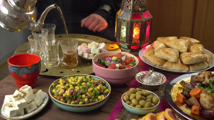 The Islamic holiday of Eid ul-Fitr marks the end of the Islamic fasting of the month of Ramadan. Traditional Eastern food and meal on the table. Muslim family eats together at home | Shutterstock HD Video #1050753490