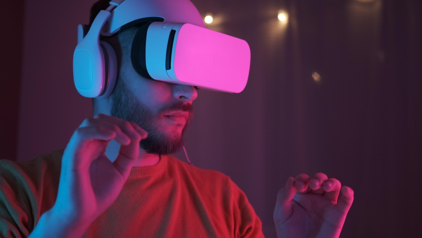 Neon light. Handsome man wearing virtual reality headset. Augmented Reality. Creative man touch something using modern 3D vr glasses indoors. Freelancer student playing using VR glasses. Closeup 4K Royalty-Free Stock Footage #1050758941