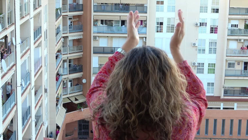 Huelva, Spain - April 19, 2020: Woman clapping on balcony as every day, at 8 PM.  Epidemic period of deadly coronavirus.