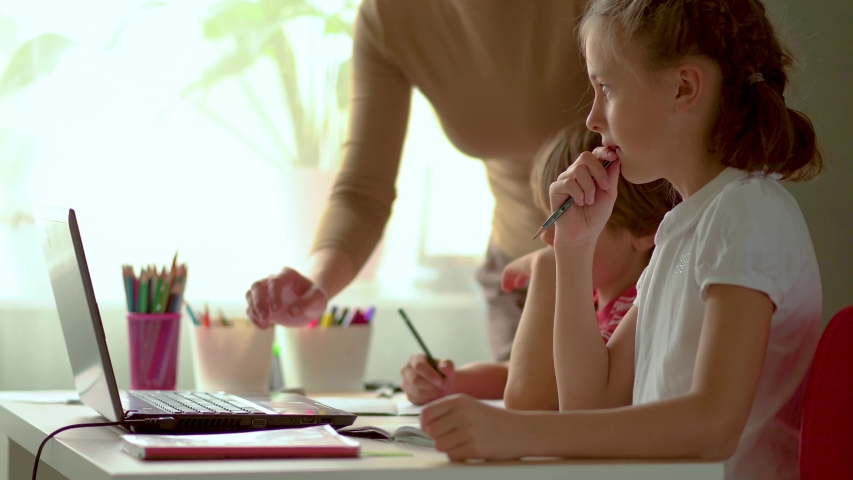 Cute children use laptop for education, online study, home studying, Boy and Girl have homework at distance learning. Lifestyle concept for Family quarantine covid-19. Mother helps daughter and son. | Shutterstock HD Video #1050776839