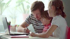 Cute children use laptop for education, online study, home studying, Boy and Girl have homework at distance learning. Lifestyle concept for Family quarantine covid-19. Father helps daughter and son.