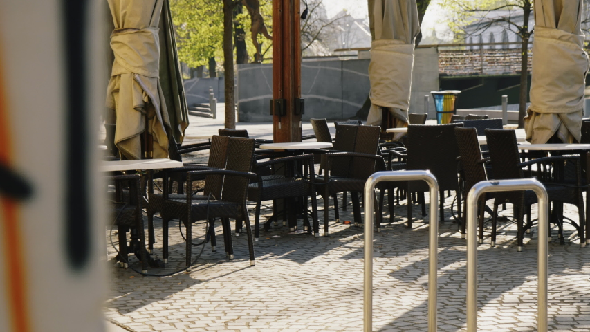 Close up shot of empty tables and chairs in the bar, restaurant, Ljubljana Royalty-Free Stock Footage #1050778612