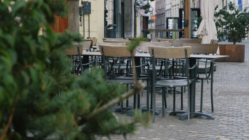 Close up shot of empty tables and chairs in the bar, restaurant, Ljubljana Royalty-Free Stock Footage #1050778645