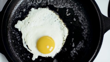 Egg frying on a cast iron pan. Sunny side up. Elegant top-down video in 4K, ideal for food and recipe videos. Download the preview for free. Shot with a RED camera.