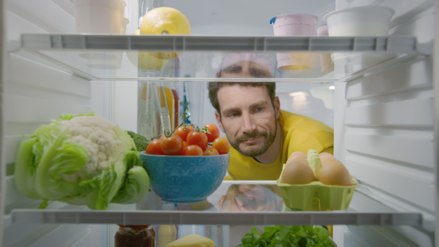 Camera Inside Kitchen Fridge: Handsome Man Opens Fridge Door, Looks inside and Disappointed Closes Door. Man Found Nothing for His Snack Time. Point of View POV Shot from Refrigerator full of Food  | Shutterstock HD Video #1050793981