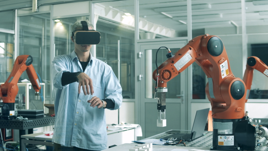 Engineer in VR-glasses is manipulating a bionic device. High school students studying robotics technologies at university lab. Royalty-Free Stock Footage #1050826246