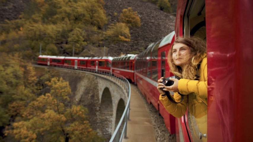 Inspiring female traveler and travel blogger look out of window of tourist train in cinematic beautiful mountains. Young beautiful woman hang out of window of red train. Excited world explorer Royalty-Free Stock Footage #1050828124