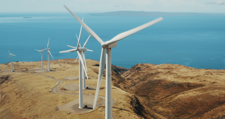 Cinematic aerial view of large wind turbines producing clean sustainable energy, clean energy future
