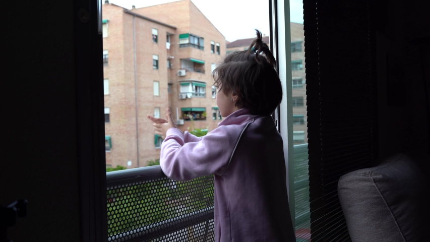 Little girl in Spain clapping in the window in support of people who fight against the coronavirus | Shutterstock HD Video #1050836323