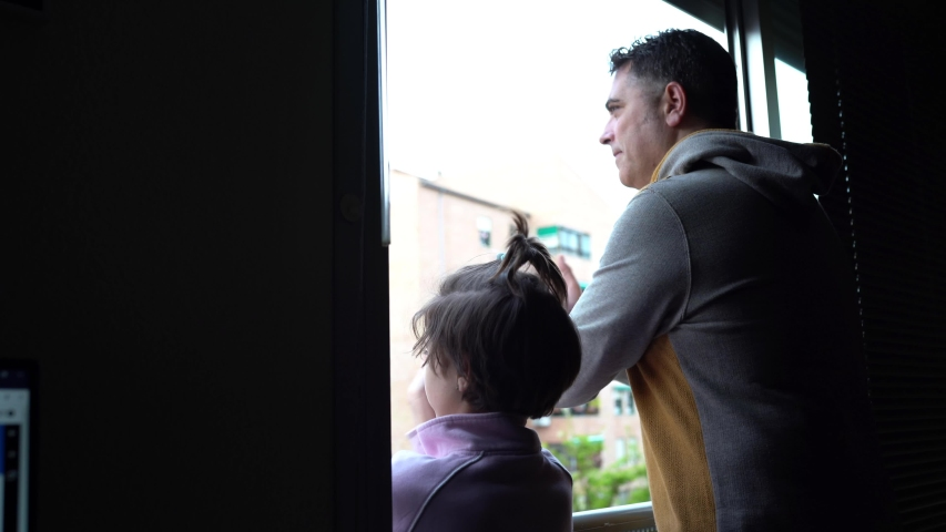 Father and daughter in Spain clapping in the window in support of people who fight against the coronavirus | Shutterstock HD Video #1050837376