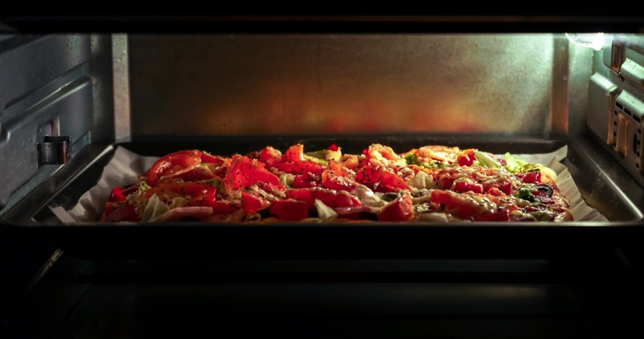 Preparation of home made pizza with a chicken, bacon, olives, cheese, in  microwave oven / time-lapse