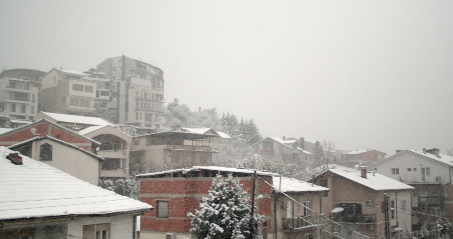 Snowing in the city. Heavy thick snow falling down on a city street in springtime, panning footage