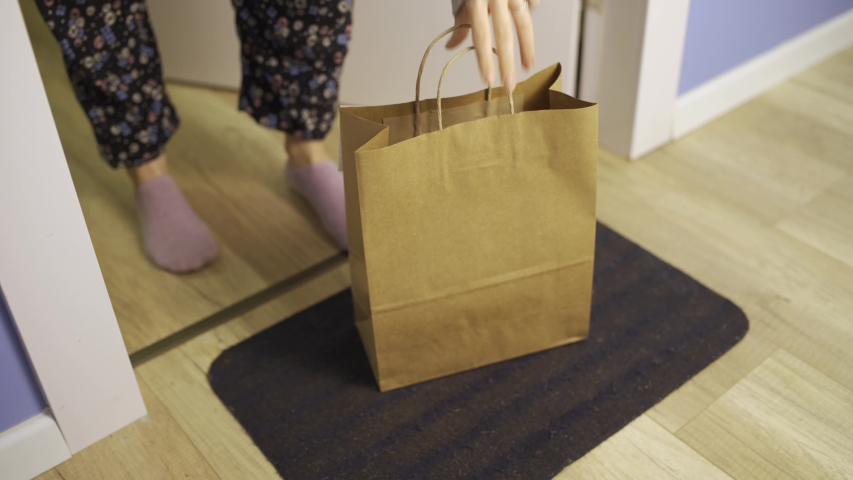 Hand with latex glove drops off package or food takeout bag - woman picks it up - package left at door front in coronavirus times - order food - no contact delivery, contactless Royalty-Free Stock Footage #1050843478