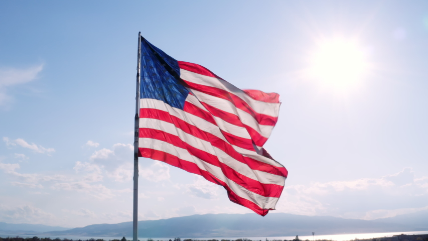 Aerial of massive American Flag slowly flapping in breeze in slow motion   Shutterstock HD Video #1050853189