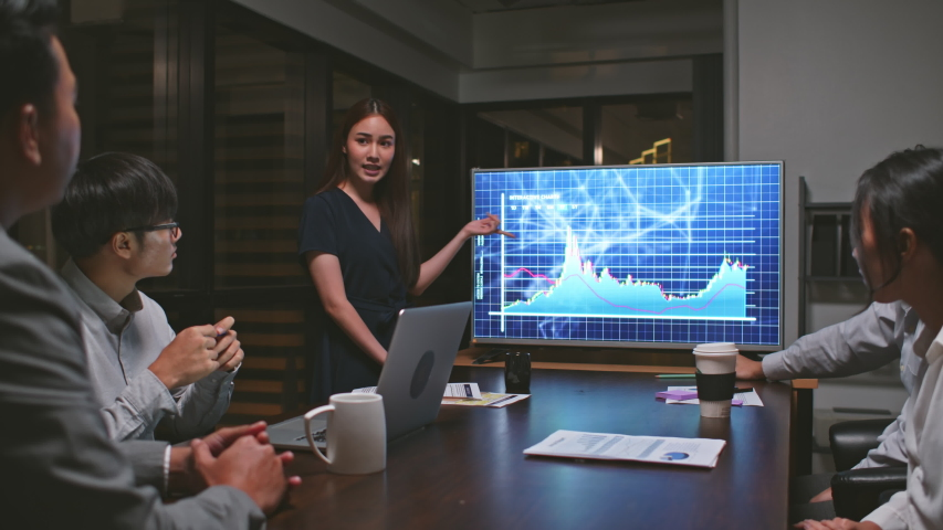 Young Asian businesswoman lead group of business financial team in strategic meeting presentation, work late night in office. Marketing strategy analysis, stock market trading, or corporate teamwork Royalty-Free Stock Footage #1050869596