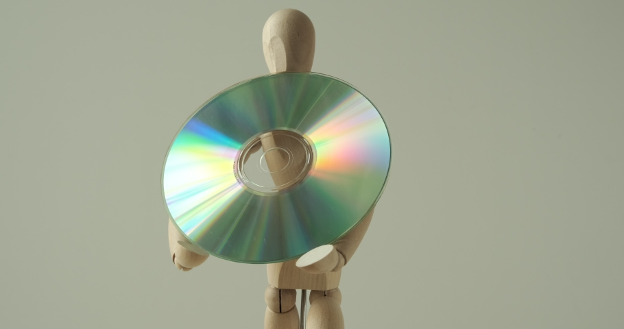Man mannequin holds a CD rom in his hands. Rotating wooden model with DVD compact disk. | Shutterstock HD Video #1050883873