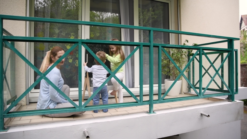 Mother with children plays on the balcony during quarantine Stay at home. Covid-19 | Shutterstock HD Video #1050887794