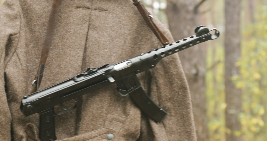 Overcoat Coat And Sub-machine Gun Of World War II Russian Soviet Infantry Red Army Soldier Hanging On A Hanger On Wood Outdoors. Uniform Of Soviet Soldiers On Eastern Front During Second World War