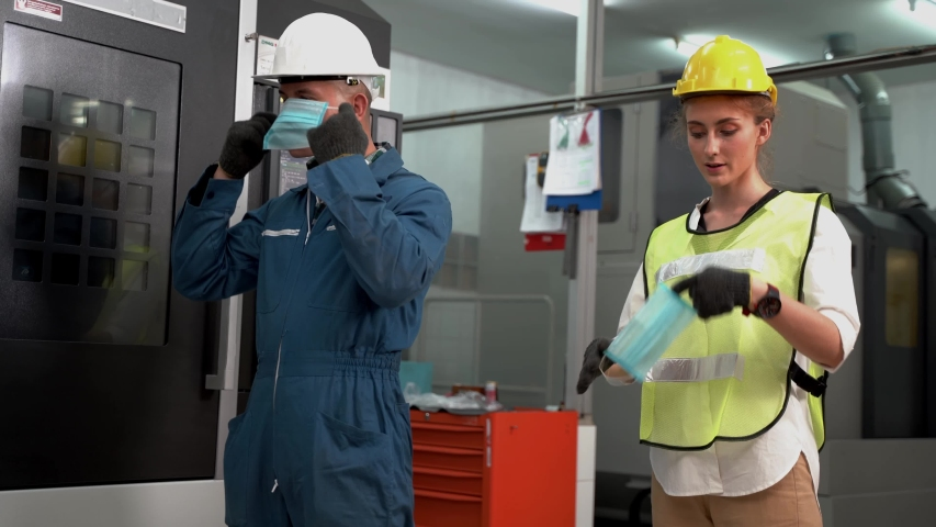 Worker Labor man and woman and wearing protection mask face and safety helmet and wearing suit green reflective safety dress in high tech clean factory. Concept of smart industry worker operating. | Shutterstock HD Video #1050907840