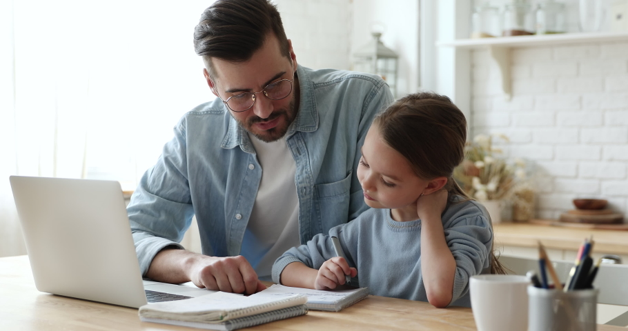 Young father checking homework helping cute school child daughter with studies sit at kitchen table. Adult parent or tutor explaining kid girl distance learning at home. Private education concept