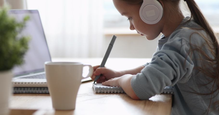 Pretty primary school girl wearing headphones distance learning at home. Focused cute kid listening audio lesson studying at table, doing homework. Children remote education on quarantine concept. Royalty-Free Stock Footage #1050934633