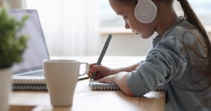 Pretty primary school girl wearing headphones distance learning at home. Focused cute kid listening audio lesson studying at table, doing homework. Children remote education on quarantine concept.