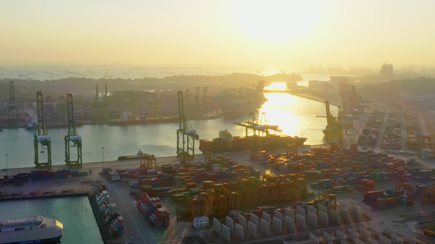 Cargo container transport ship and crane at Singapore sea port industrial district, silhouette sunset. Logistic industry, freight transportation business concept. Drone aerial high angle view panning Royalty-Free Stock Footage #1050935701