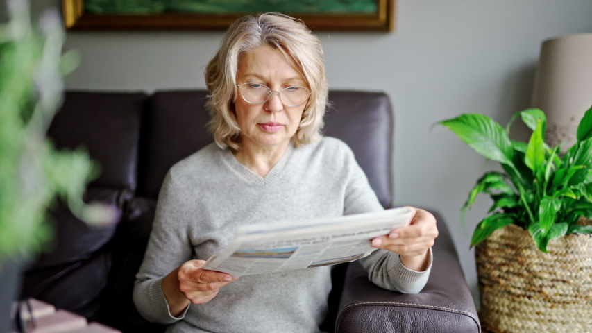 News, press, media, holidays and people concept - woman reading newspaper at home | Shutterstock HD Video #1050941656